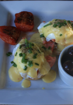 Salmon & Eggs Benedict: Poached eggs atop a split English muffin on a bed of Alaskan salmon, garnished with roasted tomatoes and black olives.