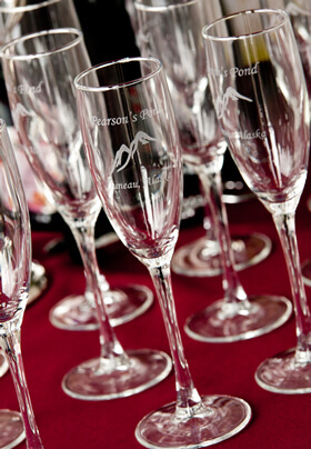 Close-up of 6 crystal clear signature champagne glasses sometimes used during hospitality hour.