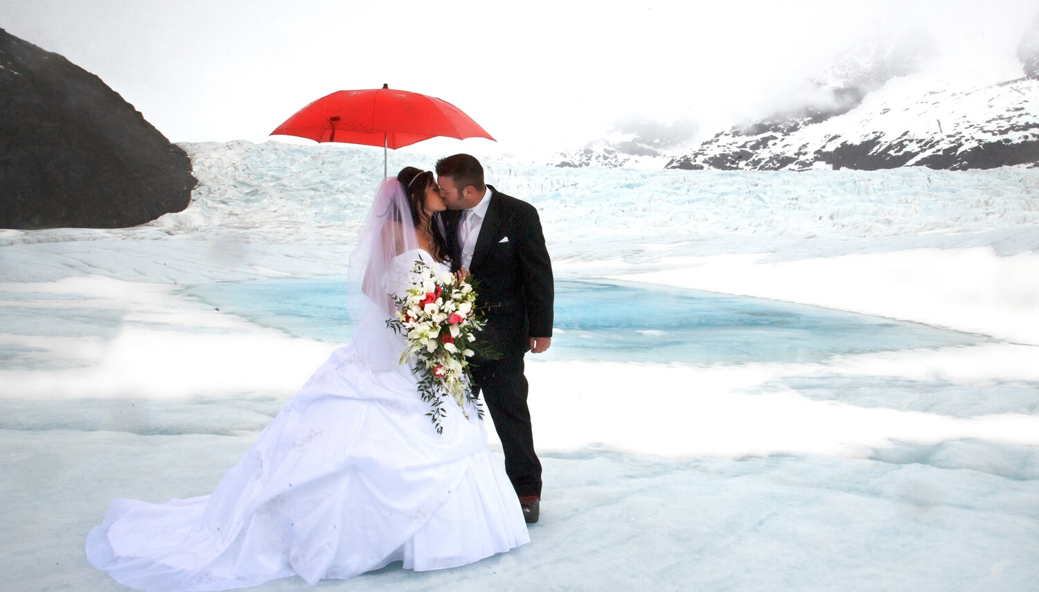 First Kiss On The Glacier Beside A Clear Blue Pond Under Bright Red Umbrella